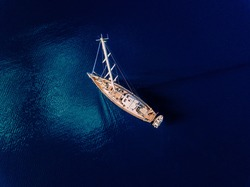 Aerial view to Yacht in deep blue sea. Drone photography