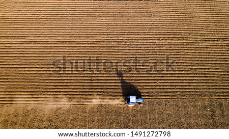 Aerial view. Tractor preparing soil for planting crops. Furrows row pattern in a crop field. #1491272798
