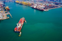 Aerial view Tugboat pushing container ship to quayside for load and unload container via crane for logistics, import export, shipping or transportation international on green sea Asia pacific
