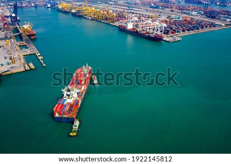 Aerial view Tugboat pushing container ship to quayside for load and unload container via crane for logistics, import export, shipping or transportation international on green sea Asia pacific Foto stock ©