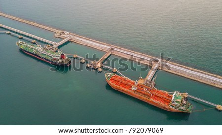 Aerial view two tanker ship at the port terminal, oil terminal is industrial facility for storage of oil and petrochemical products ready for transport to further storage facilities.