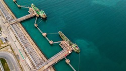 Aerial view two tanker ship loading in port, tanker ship under cargo operations on typical shore station with clearly visible mechanical loading arms and pipeline infrastructure.