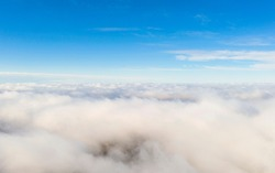 Aerial view white clouds in blue sky. Aerial top view cloudscape. Texture of clouds. Sunrise or sunset over clouds. Panorama clouds