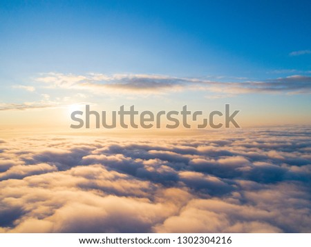 Aerial view White clouds in blue sky. Top view. Drone. Aerial bird's eye fly. Aerial top view cloudscape. Texture of clouds. View from above. Sunrise or sunset over clouds. Panoramic