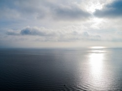 Aerial view White clouds in blue sky. Top view. View from drone. Aerial bird's eye. Aerial top view cloudscape. Texture of clouds. Look from above. Sunrise over the sea
