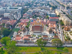 Aerial View With Drone. Wat Ratchanatdaram and Loha Prasat Metal Castle in the twilight time, Landmark of Bangkok Thailand. Moment of Democracy monument at Dusk.