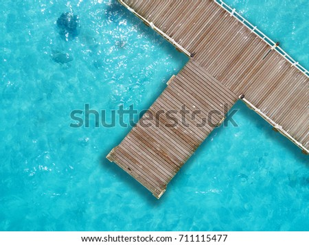 aerial view, wooden bridge laying to the sea with cleared water for swimming in island