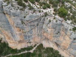 Aerial views of the Mont-Rebei canyon with the cliffs, stairs on the walls, the lake, and the path along the canyon