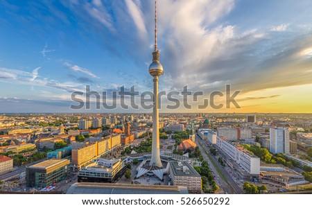 Aerial wide angle view of Berlin skyline with famous TV tower at Alexanderplatz and dramatic clouds in beautiful golden evening light at sunset in summer, Germany