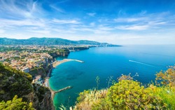 Aerial wide angle view of cliff coastline Sorrento and Gulf of Naples, Italy. Clear azure sea and luxury hotels of Sorrento attract lot of tourists from all over world.