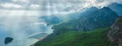 Aerial wide angle view of mountain panorama in Antalya city, Turkey, Sunny blue sky, white clouds, sunrays and sunbeams through clouds, sparkling blue sea water. Horizontal color photography.