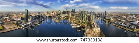 Aerial wide panorama of Melbourne Docklands area over Yarra river waters with marina yachts and wharfs. Modern urban high-rise towers and architecture on CBD waterfront.