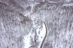 Aerial winter landscape with winding curvy road and meandering mountain stream