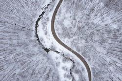 Aerial winter landscape with winding curvy road parallel to a meandering mountain stream