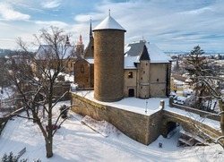 Aerial, winter view of an authentic renaissance castle Sternberk and its gothic fortification covered by snow against blue sky. Czech landscape, Central Moravia, Czech republic.