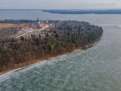 Aerial winter view of Pazaislis monastery in Kaunas, Lithuania. With icy Kaunas lake with cracked ice around the cape