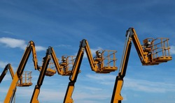 Aerial work platforms lined up against blue sky with clouds