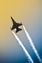 aerobatic military jet in a gradient sky leaving a smoke trail