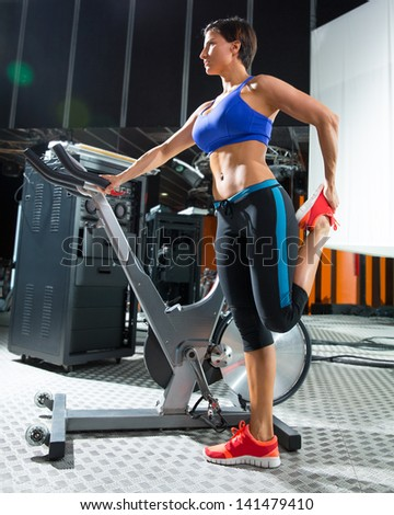 Aerobic woman stretching exercises after workout at gym
