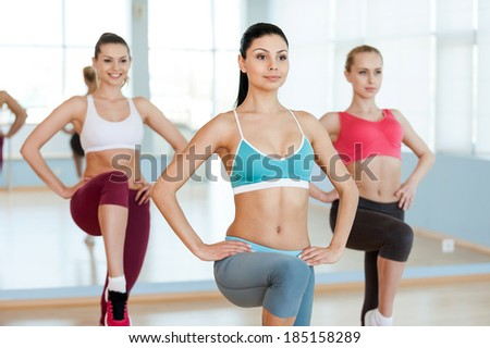 Aerobics class Three beautiful young women in sports clothing exercising together and smiling