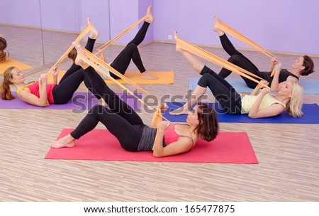 Aerobics HOT pilates group with rubber bands in a row at fitness gym