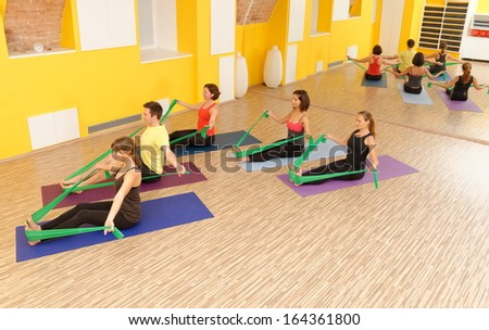 Aerobics pilates group with rubber bands in a row at fitness gym