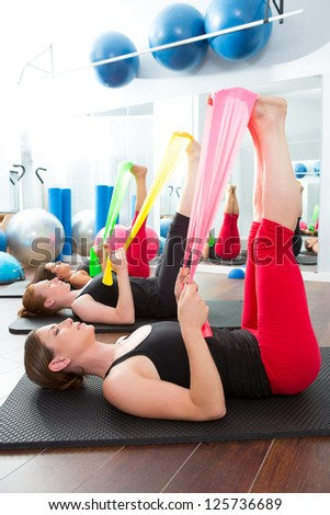 Aerobics pilates women group with rubber bands in a row at fitness gym