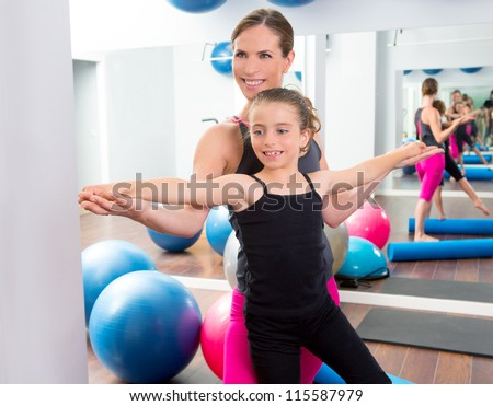 Aerobics woman personal trainer of children girl stability with foam roller
