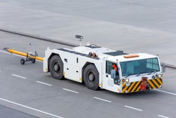 Aerodrome tow tractor is driving along the steering paths at the airport