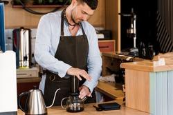 Aeropress coffee: barista press to device and coffee drops pours trought aeropress to pot. Alternative coffee brewing method. Handsome bearded barista makes tasty Scandinavian coffee