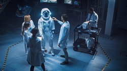 Aerospace Facility: Scientists, Engineers Wearing White Coats have Discussion, Use Computers, Construct Astronaut Helmet for New Space Suit Adapted for Exploration and Travel. Elevated High Angle Shot