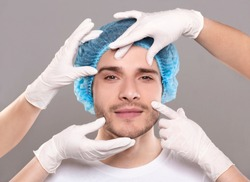 Aesthetic Cosmetology concept. Doctor's hands in gloves touching face of handsome young man, closeup