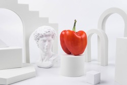 Aesthetic food photography on trendy white podium. Minimal food art still life concept.  Greek statue and sweet bell pepper on white background.