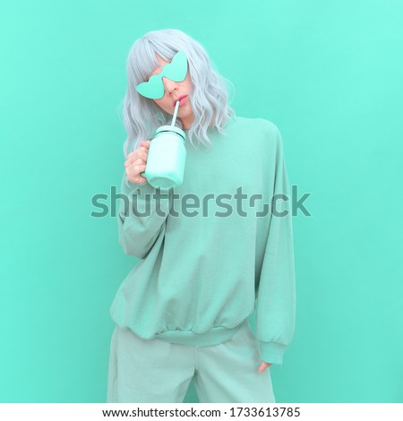 Aesthetic girl in stylish accessories sunglasses and fresh Smoothie. Aqua Menthe monochrome colours design