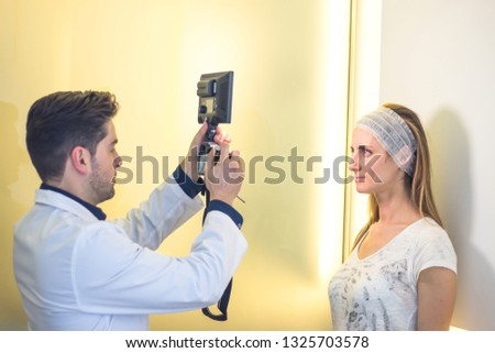 Aesthetic medicine concept. Doctor taking photo to the patient before treatment.
