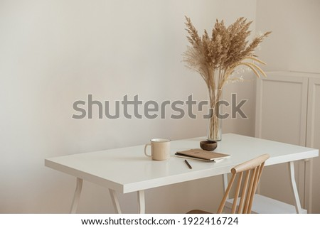 Aesthetic minimal office workspace interior design. Mug, notebook, pampas grass floral bouquet on white table against white wall. Girl, woman boss work at home business concept.