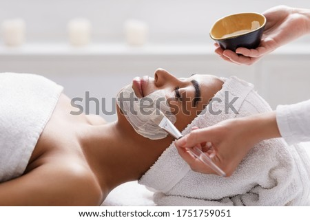 Aesthetic Procedure. Beautician Applying Clay Face Mask On Black Woman Face, Side View