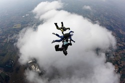 Aff instructors with student over a big cloud in free fall
