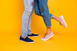 Affection feelings daydream meeting weekend holiday concept. Cropped portrait of legs in jeans sneakers, lovely romantic couple kissing hugging isolated on yellow background