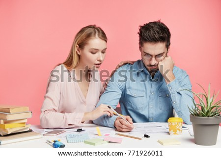 Affectionale lovely female tries to help her husband, looks attentively what man writes, wants to give some advice how make financial report correctly and encourage him. People and team work concept