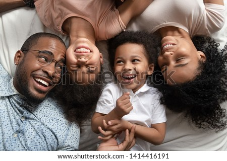 Affectionate african american parents and cute small kids laughing lying on bed together, happy mixed race family with children bonding having fun enjoy funny moments in bedroom, top view from above