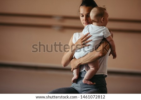 Affectionate athletic mother holding baby boy in her arms in health club. Copy space.