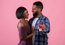 Affectionate black couple hugging and looking at each other, holding box with engagement ring on pink studio background, selective focus. Marriage proposal, wedding concept