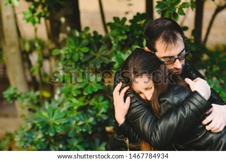 Affectionate boyfriend hugging his girlfriend after she receives sad and depressing news.