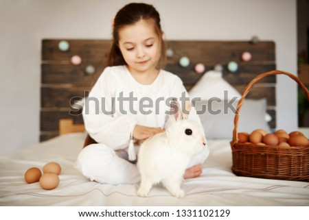 Affectionate child stroking the rabbit  #1331102129