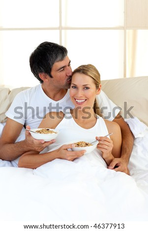 Affectionate couple eating cereals lying in the bed at home