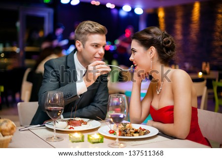 Affectionate couple in restaurant him feeding she