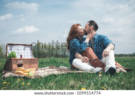 Affectionate couple is kissing while relaxing in the nature together. Their eyes are closed with love and passion   #1099514774