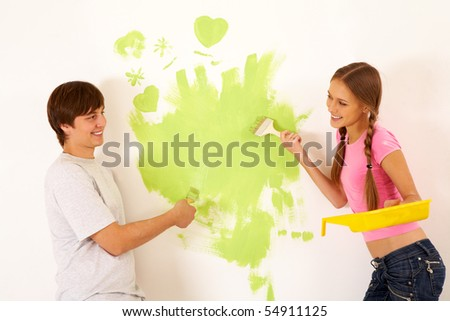 Affectionate couple looking at each other while painting walls in new house