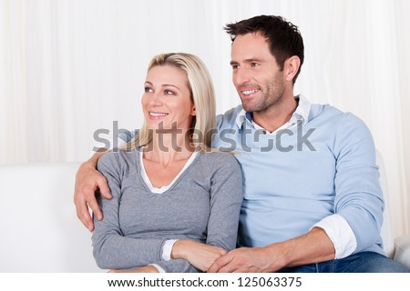 Affectionate couple relaxing on a sofa with the mans arm around his wifes shoulders as she rests her head on his shoulder